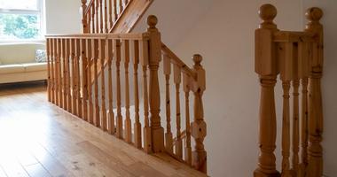 Прямая деревянная лестница на второй этаж из дуба с оригинальным ограждением